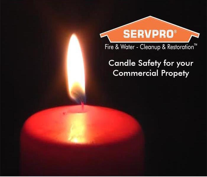 Close up of a lit candle with SERVPRO logo in the backgeound