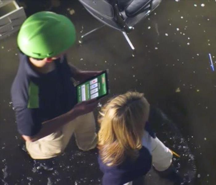 SERVPRO employee walking through water damaged business with owner