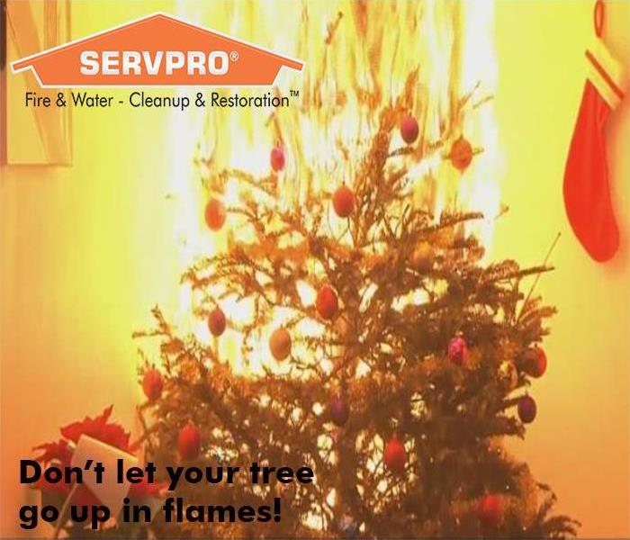 A close up of a Christmas tree on fire with a SERVPRO logo